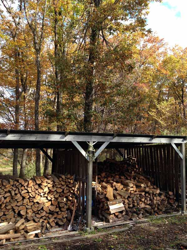 我が家の薪小屋。薪小屋の周りの広葉樹がきれいに色づいた頃に毎年薪ストーブの火入れをします