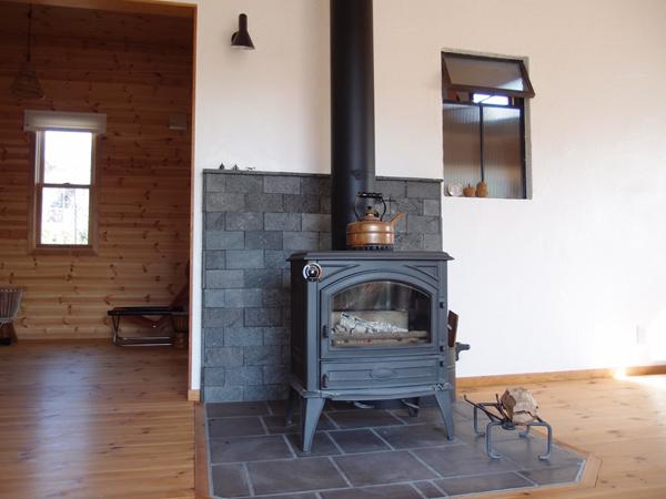 M様邸の薪ストーブはベルギー製ドブレ640CBJ。ストーブと炉台レンガと背面のアイアンフレームのガラスのカラーをさりげなくブラックで統一。「やるなお主」です。