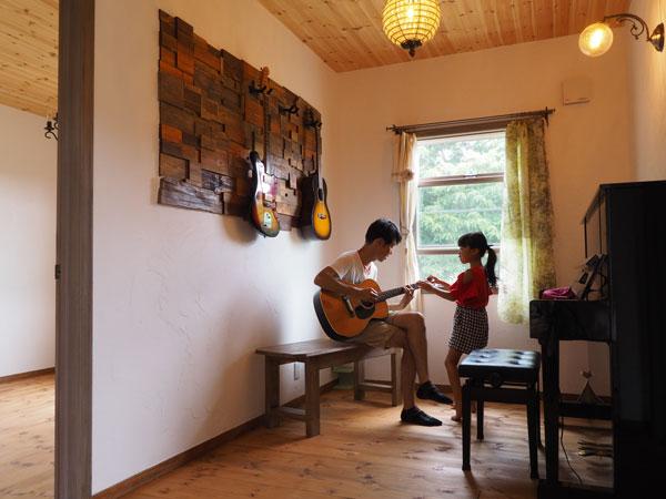 ご家族の趣味の音楽ルーム、ギターが掛けられた壁の造作も内外装の余り材をタイル状にして貼ったご主人ご自慢の秀作